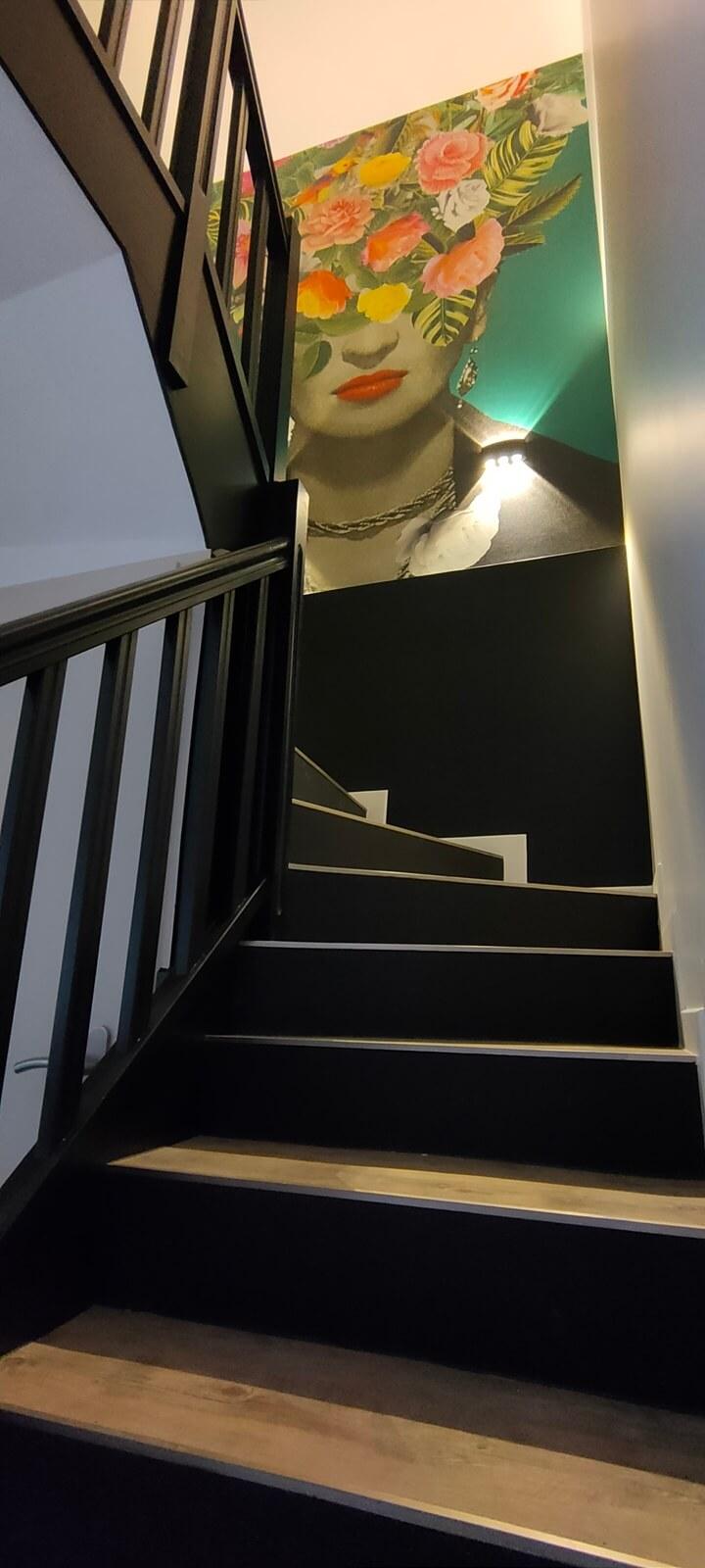 Une montée d'escalier avec des marches en bois, une rampe peinte en noir, des murs blancs et noirs décorés d'un tableau Frida Kahlo après home staging