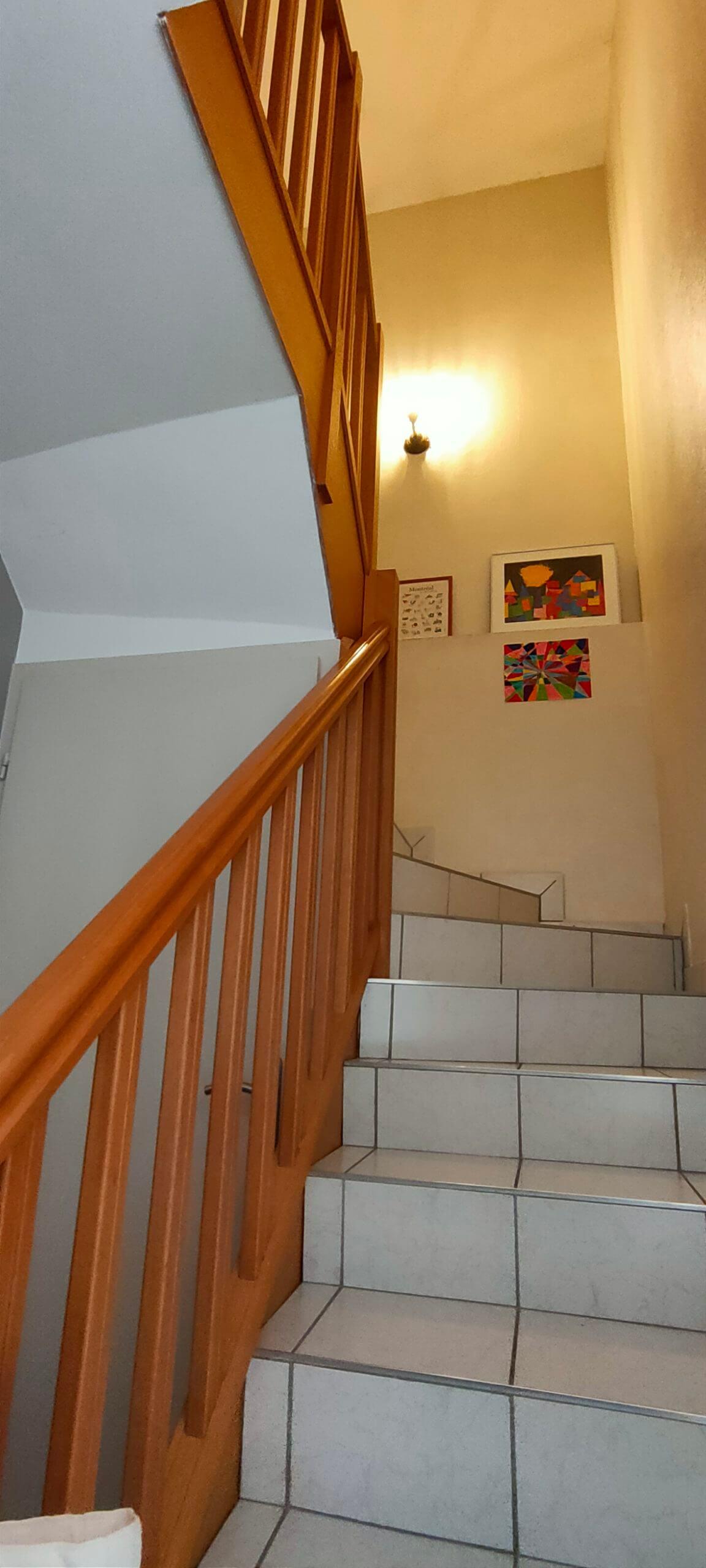 Une montée d'escalier avec des marches en carrelage blanc, une rampe couleur chêne et des murs jaunes clairs avant un home staging