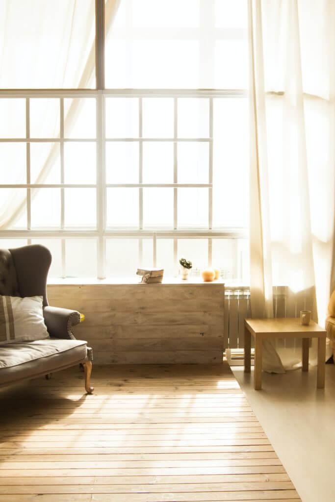 Un salon baigné de lumière avec fauteuil bas, table basse et parquet