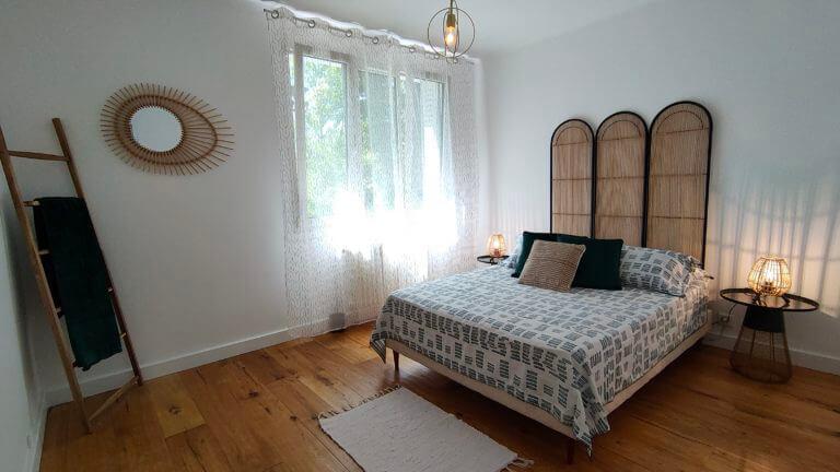 Une chambre avec un lit double, un paravent tressé en tête de lit et de la décoration en bois après un home staging