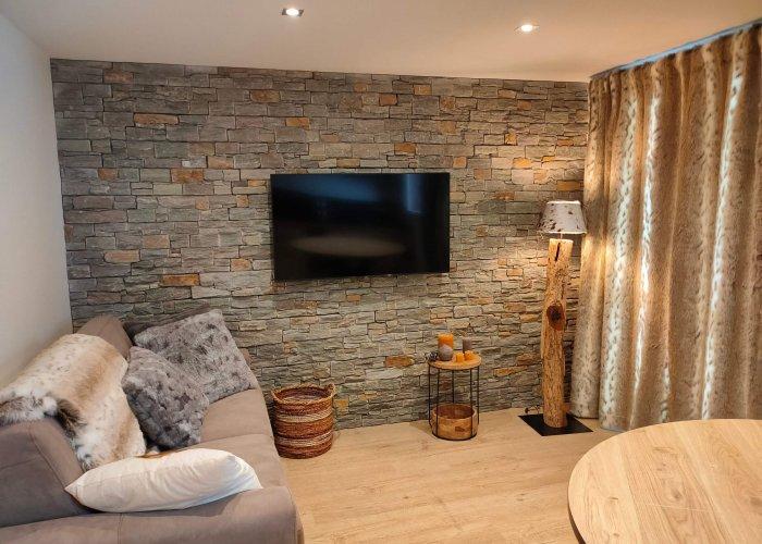 Le salon d'un meublé touristique dans les tons lin et taupe avec un canapé, un lampadaire et un mur en parements après un home staging