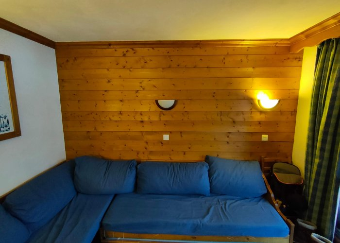 Le salon d'un meublé touristique avec canapé d'angle et lambris avant un home staging