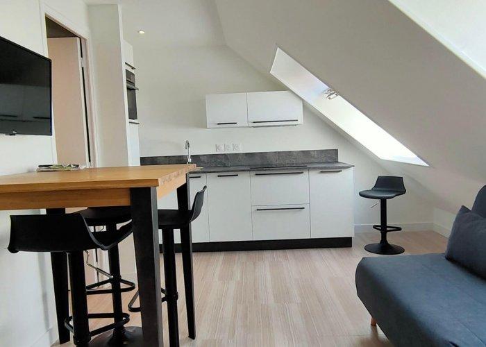 Un appartement sous les combles avec une cuisine intégrée et un coin salon après home staging