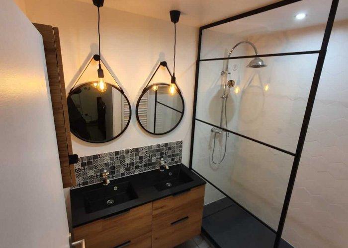Une salle de bain avec meuble en bois double vasques et une douche moderne après rénovation