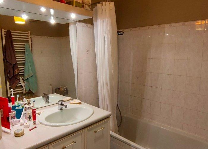Une salle de bain avec un meuble simple vasque et une baignoire avant rénovation