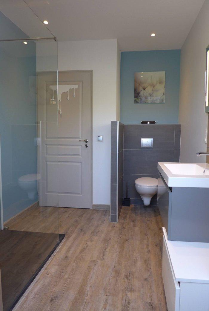 Une salle de bain blanche et bleu ciel avec toilette après une rénovation